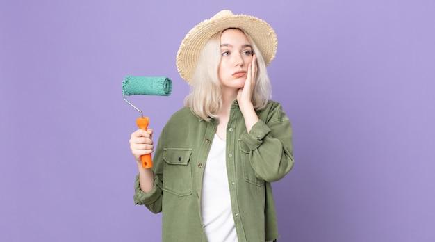 Mulher jovem e bonita albina se sentindo entediada, frustrada e com sono depois de uma pintura cansativa e segurando um rolo de tinta