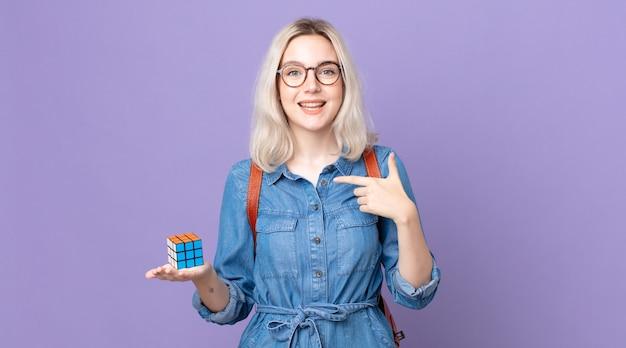 Mulher jovem e bonita albina se sentindo feliz e apontando para si mesma com um jogo de inteligência animado e resolvendo