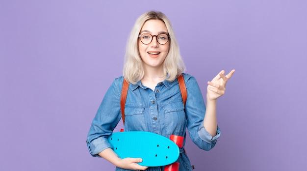Mulher jovem e bonita albina se sentindo feliz, surpresa ao perceber uma solução ou ideia e segurando um skate