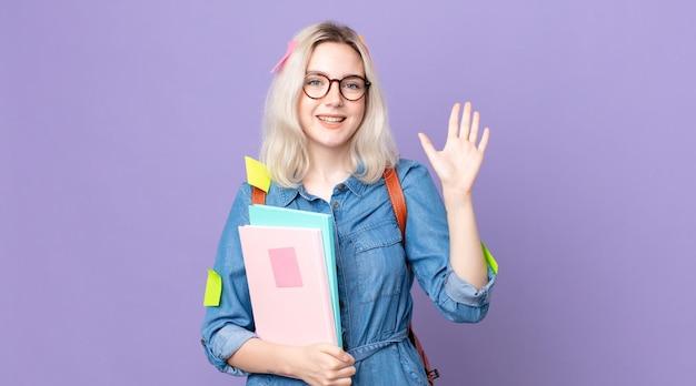 Mulher jovem e bonita albina sorrindo alegremente, acenando com a mão, dando as boas-vindas e cumprimentando você. conceito de estudante