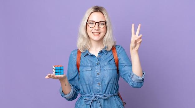 Mulher jovem e bonita albina sorrindo e parecendo feliz, gesticulando vitória ou paz e resolvendo um jogo de inteligência