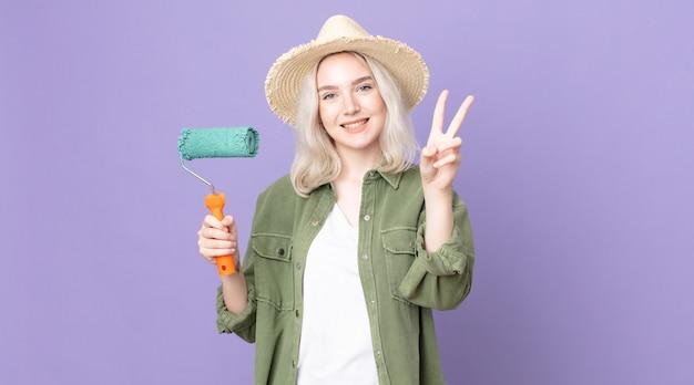 Mulher jovem e bonita albina sorrindo e parecendo feliz, gesticulando vitória ou paz e segurando um rolo de tinta