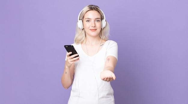 Mulher jovem e bonita albina sorrindo feliz com simpatia e oferecendo e mostrando um conceito com fones de ouvido e smartphone