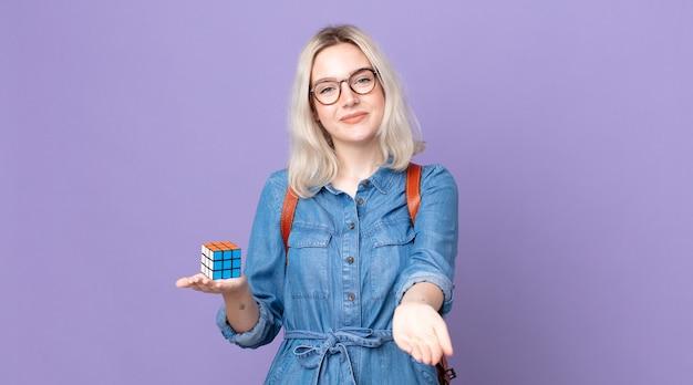 Mulher jovem e bonita albina sorrindo feliz com simpatia e oferecendo e mostrando um conceito e resolvendo um jogo de inteligência