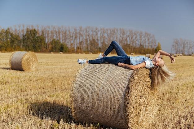 Mulher jovem e bonita aldeã posando de jeans em um fardo de feno em um campo