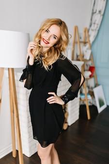 Mulher jovem e bonita alegre com cabelo loiro ondulado, posando em um quarto moderno. usando um elegante vestido preto com mangas compridas. lareira, abajur branco
