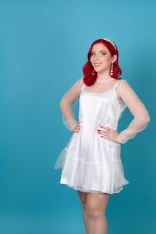 Mulher jovem e bonita alegre com cabelo ruivo e mãos na cintura em um vestido de malha de seda branca