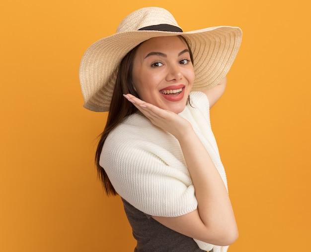 Mulher jovem e bonita alegre com chapéu de praia em pé na vista de perfil, tocando o queixo isolado na parede laranja