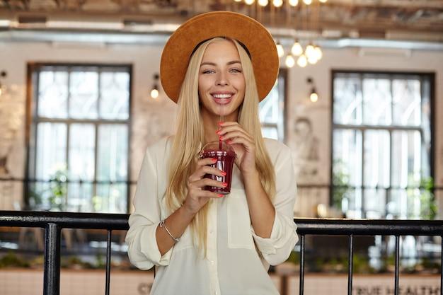 Mulher jovem e bonita alegre com longos cabelos loiros olhando feliz enquanto posava sobre o interior do café, segurando uma xícara de limonada nas mãos