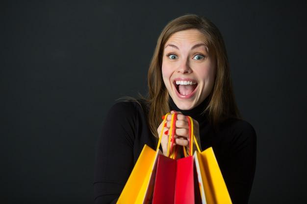 Mulher jovem e bonita alegre com pacotes nas mãos em um fundo preto