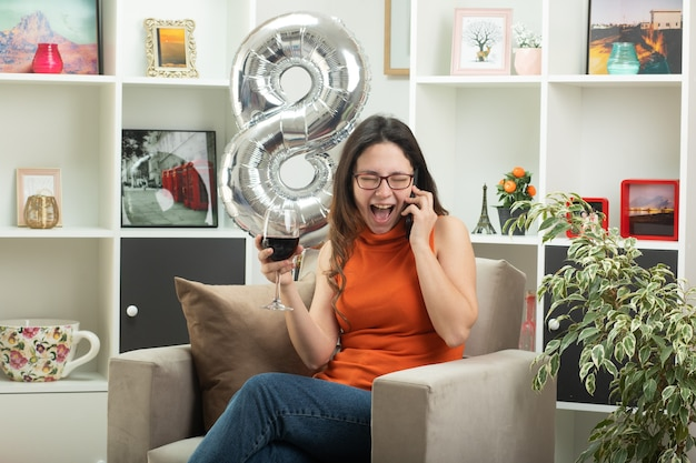 Mulher jovem e bonita alegre de óculos falando no telefone e segurando uma taça de vinho, sentada na poltrona na sala de estar em março, dia internacional da mulher