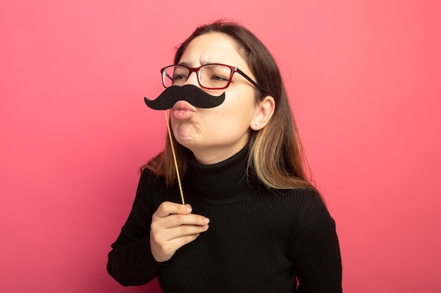 Mulher jovem e bonita alegre em uma blusa de gola alta preta e óculos segurando um bigode engraçado, mandando um beijo em pé sobre uma parede rosa