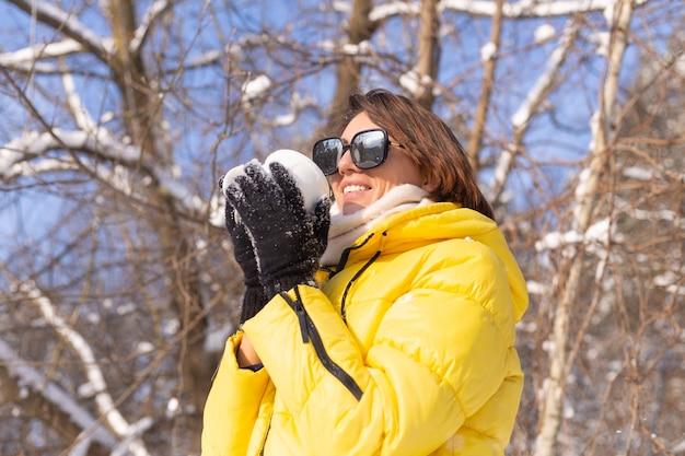 Mulher jovem e bonita alegre em uma floresta de inverno com neve em óculos de sol e um copo cheio de neve se divertindo