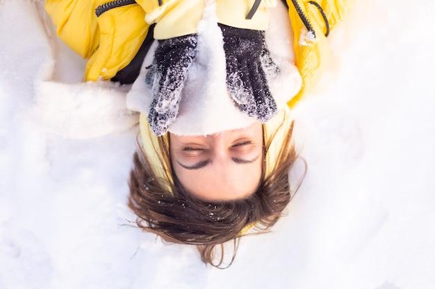 Mulher jovem e bonita alegre em uma floresta de inverno com neve, se divertindo, se alegra no inverno e neve em roupas quentes