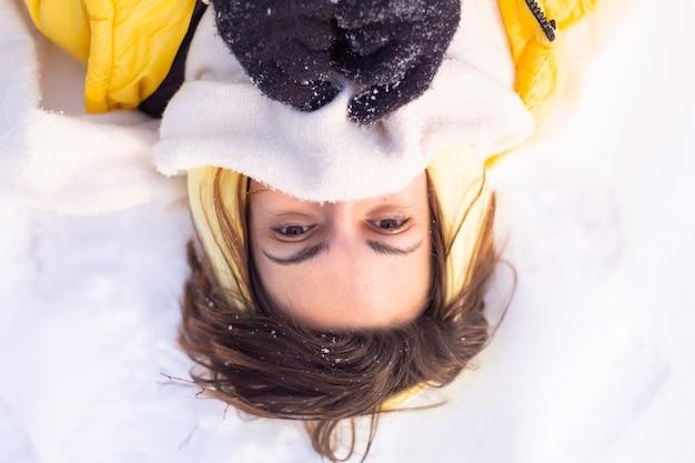 Mulher jovem e bonita alegre em uma floresta de inverno com paisagem de neve, se divertindo, se alegra no inverno e neve em roupas quentes, lenço