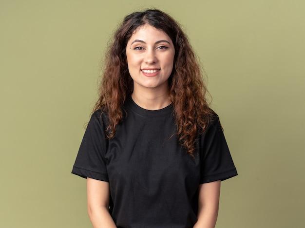 Mulher jovem e bonita alegre olhando para a frente sorrindo isolada na parede verde oliva