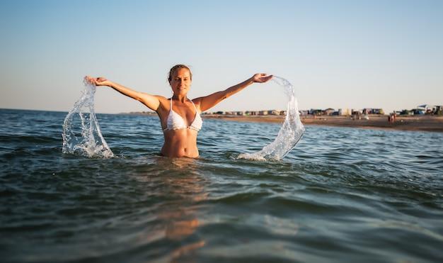 Mulher jovem e bonita alegre se banha em água e se alegra, levantando as mãos na ensolarada noite quente de verão. conceito de desfrutar de umas férias tão esperadas. copyspace