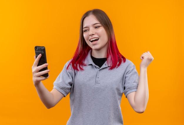 Mulher jovem e bonita alegre vestindo uma camiseta cinza olhando para o telefone na mão, mostrando um gesto de sim na parede amarela isolada