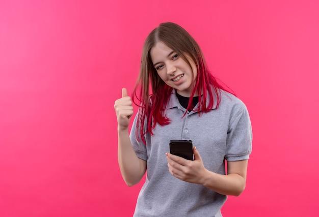 Mulher jovem e bonita alegre vestindo uma camiseta cinza segurando um telefone e mostrando um gesto de sim na parede rosa isolada