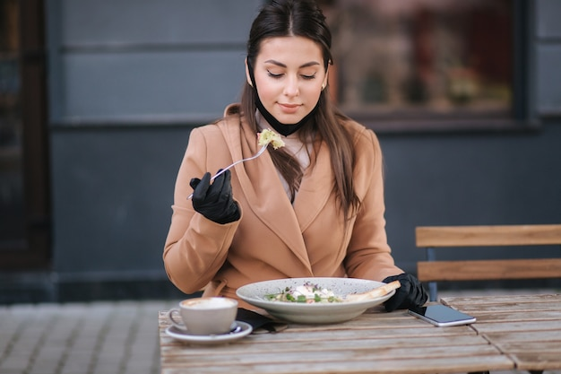 Mulher jovem e bonita almoçando em um café ao ar livre no terraço. mulher em máscara protetora preta.