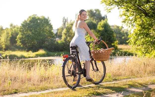 Mulher jovem e bonita andando de bicicleta à beira do rio em um dia quente de sol