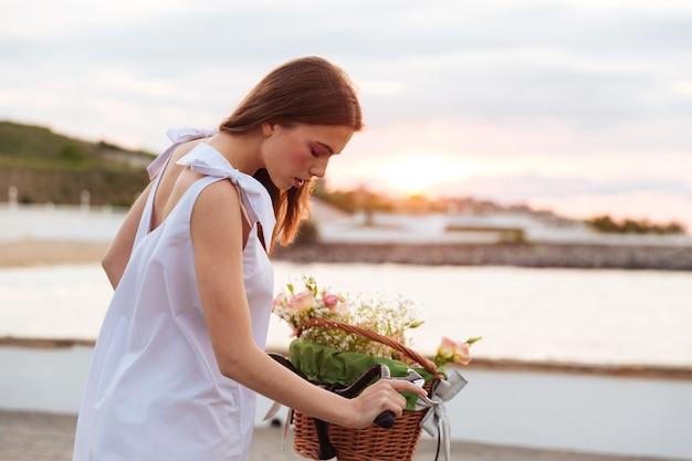 Mulher jovem e bonita andando de bicicleta no promende no verão