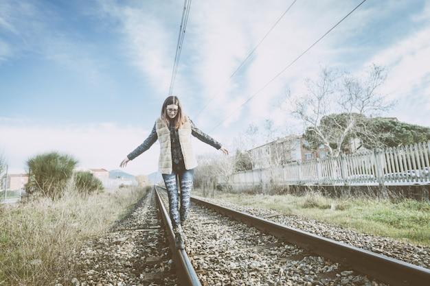 Mulher jovem e bonita andando em equilíbrio em trilhos.