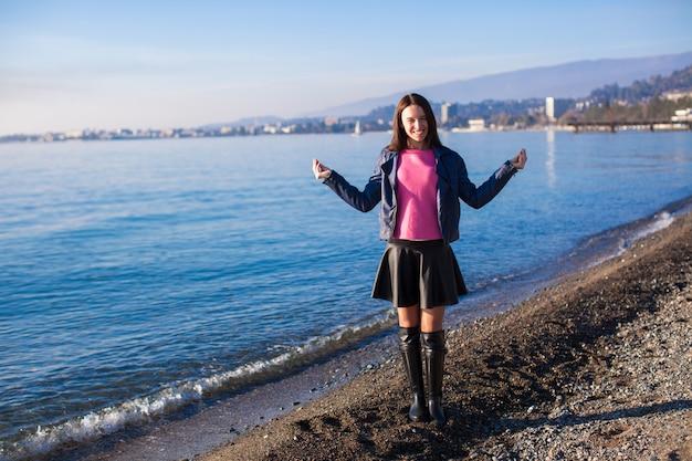 Mulher jovem e bonita andando na praia em dia de sol de inverno sozinho