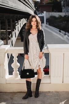 Mulher jovem e bonita andando na rua com roupa da moda, segurando bolsa, vestindo jaqueta de couro preta e vestido de renda branca estilo primavera outono, corpo inteiro