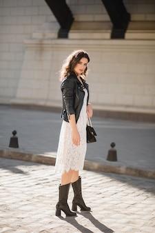 Mulher jovem e bonita andando na rua com roupas da moda, segurando bolsa, vestindo jaqueta de couro preta e vestido de renda branca, estilo primavera-outono, corpo inteiro, posando, botas de couro