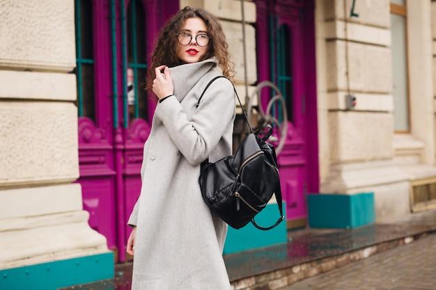 Mulher jovem e bonita andando na rua da cidade com casaco cinza, estilo de moda outono, óculos, mochila,
