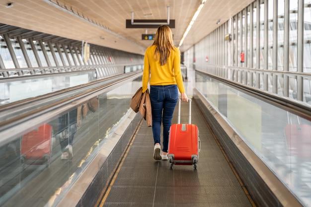 Mulher jovem e bonita andando para trás para o aeroporto ou estação com sua bagagem