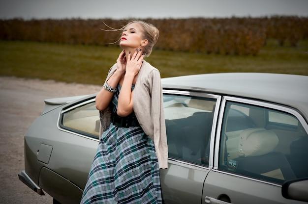 Mulher jovem e bonita andando perto do carro retrô perto do campo de lavanda em estilo francês