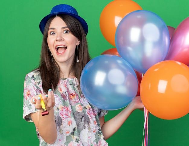 Mulher jovem e bonita animada com chapéu de festa segurando balões com apito de festa isolado na parede verde