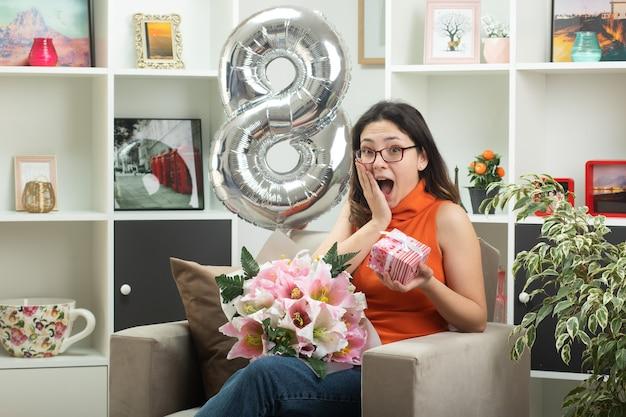 Mulher jovem e bonita animada de óculos segurando um buquê de flores e uma caixa de presente, sentada na poltrona na sala de estar em março, dia internacional da mulher