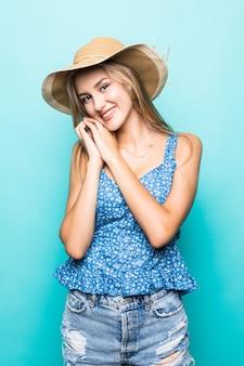Mulher jovem e bonita animada em pé de chapéu de palha isolado sobre fundo azul.