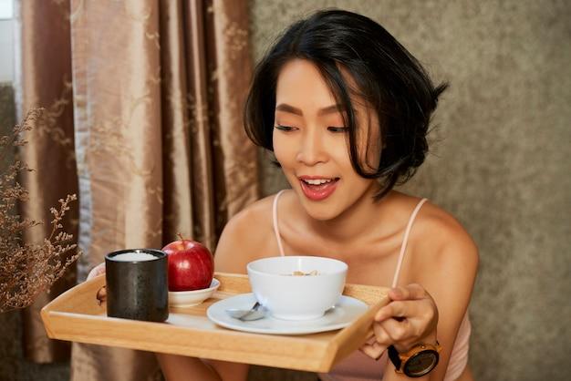 Mulher jovem e bonita animada olhando para a bandeja com café da manhã saudável composto por mingau, xícara de chá e maçã madura