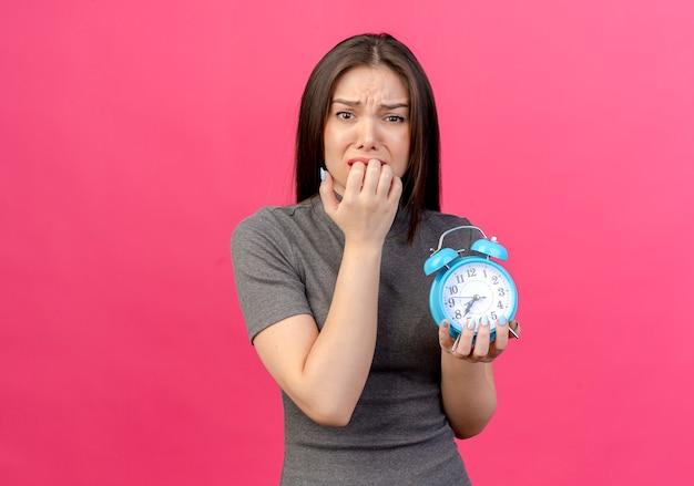 Mulher jovem e bonita ansiosa segurando o despertador e mordendo os dedos, isolado em um fundo rosa com espaço de cópia