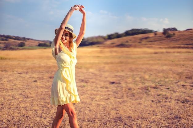 Mulher jovem e bonita ao ar livre na colina em um dia de verão