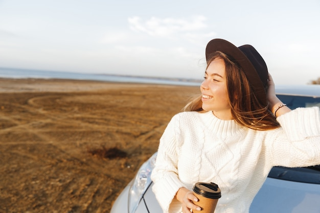 Mulher jovem e bonita ao ar livre na praia durante o pôr do sol, sentada em um carro, bebendo café