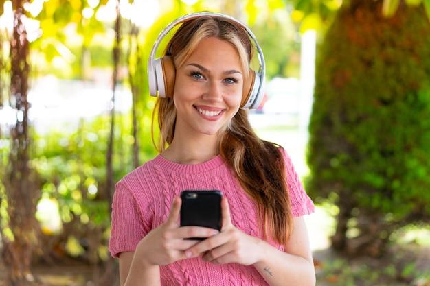 Mulher jovem e bonita ao ar livre ouvindo música com um celular e olhando para a frente
