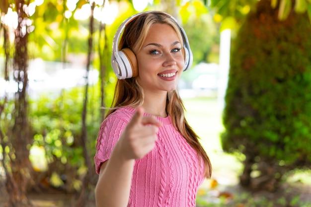 Mulher jovem e bonita ao ar livre ouvindo música e apontando para a frente