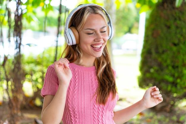 Mulher jovem e bonita ao ar livre ouvindo música e dançando