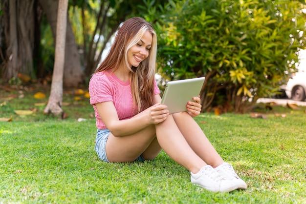 Mulher jovem e bonita ao ar livre segurando um tablet
