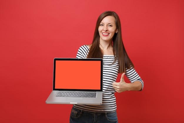 Mulher jovem e bonita aparecendo o polegar, segurando o computador laptop pc com tela vazia preta em branco isolada no fundo da parede vermelha brilhante. emoções sinceras de pessoas, conceito de estilo de vida. simule o espaço da cópia.