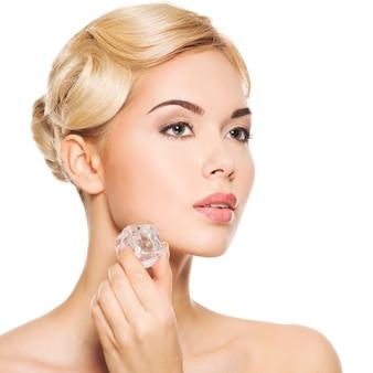 Mulher jovem e bonita aplica o gelo no rosto. conceito de cuidados com a pele. isolado no branco.