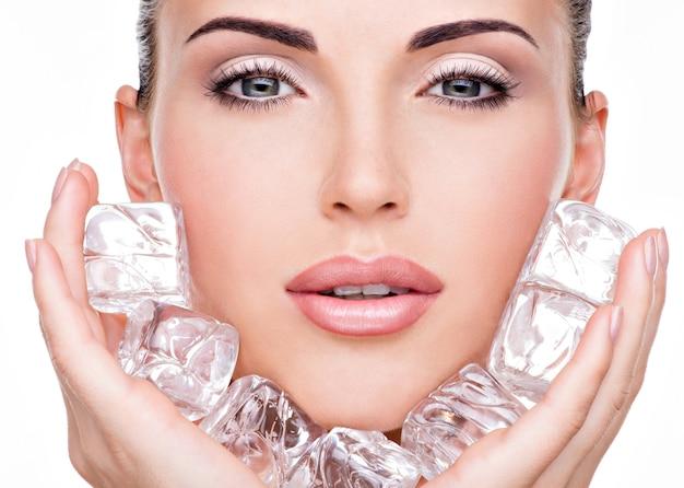 Mulher jovem e bonita aplica o gelo no rosto. conceito de cuidados com a pele.