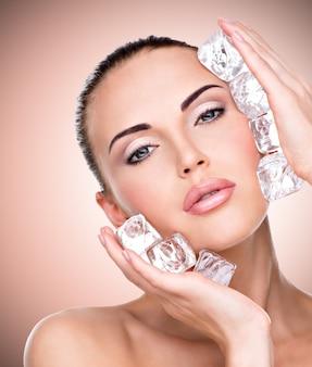 Mulher jovem e bonita aplica o gelo no rosto.