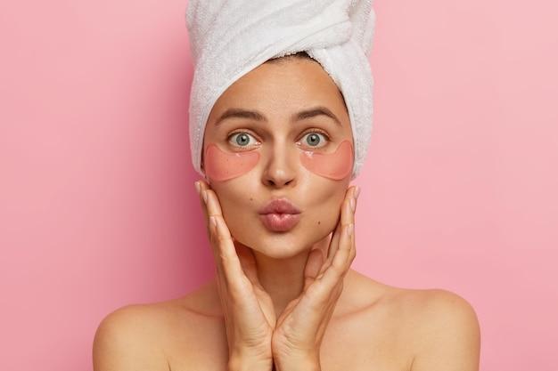 Mulher jovem e bonita aplicando adesivos de hidrogel sob os olhos