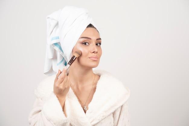 Mulher jovem e bonita aplicando base no rosto com borla